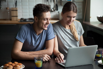 Young couple using laptop together having breakfast at home, man and woman communicating in social network, searching for new sale offers or shopping in online computer application in the kitchen