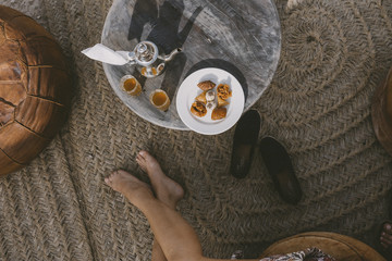 Woman sitting next to table with tea and cookies