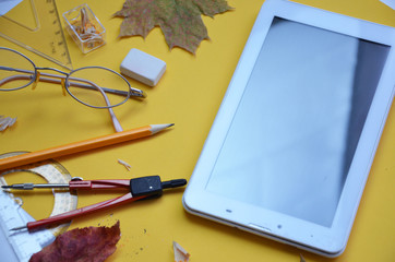 Back to school and technology banner with digital touch screen tablet and colorful stationery. autumn leaves, compasses, pencil, sharpener on a yellow background, top view, copy space, mock up