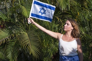 A young and attractive Caucasian girl holding a flag of Israel, green palm background. The Israel Independence day, salute, celebration.
