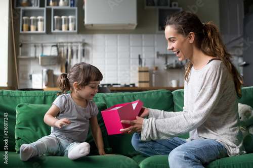 Smiling Mom Giving Excited Daughter Present On Her Birthday Happy Single Mother And Curious Child Girl Opening Pink Gift Box Together Cute Kid Receiving