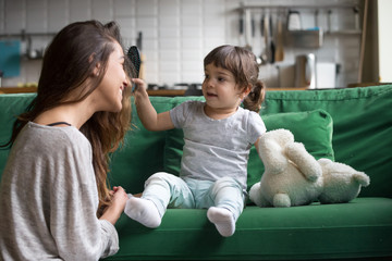Cute kid girl brushing mothers hair having fun together on sofa, little daughter holding brush helping young happy single mom with hairstyle playing at home, child and mommy funny activity concept