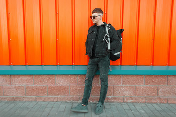 Handsome young man in black fashion clothes with a stylish backpack near the orange wall