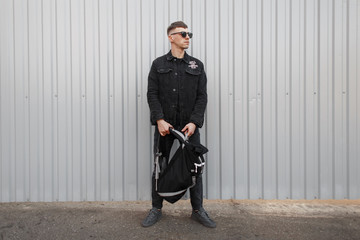 Fashionable young man with trendy sunglasses in a black stylish denim jacket with black jeans with a backpack near the gray metal fence