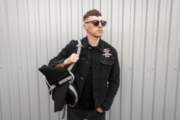 Handsome young man in a black denim jacket with a T-shirt in stylish sunglasses stands near a gray wall on the street