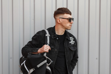 Stylish young handsome model man with black glasses in a black denim jacket with a T-shirt with a bag near the gray metal wall