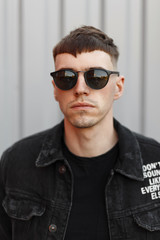 Stylish young hipster man in sunglasses with a hairstyle in a black denim jacket and a T-shirt on the street