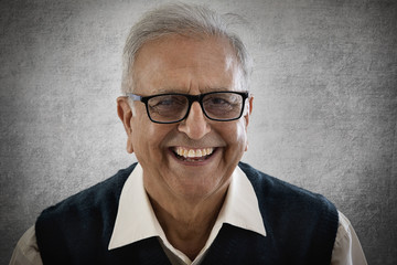 Portrait of smiling elderly man wearing spectacles