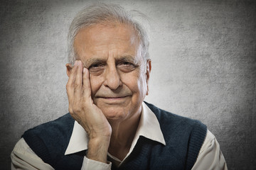 Portrait of smiling senior man with hand on face