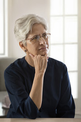 Mature woman thinking with hand on chin