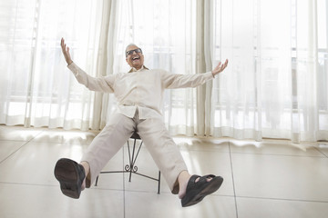 Smiling senior man sitting in chair with arms and legs outstretched