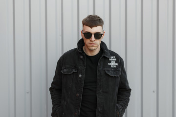young brutal bad man with a hairstyle with black glasses and black fashionable denim clothing near the gray wall