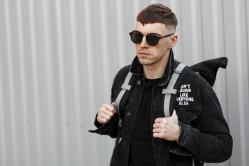 Handsome young man in black sunglasses and black denim clothing with a backpack near the gray wall