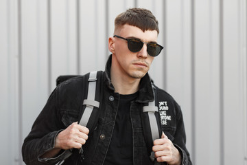 Handsome young hipster man in stylish sunglasses and a black denim fashion jacket with a bag on the street near the gray wall