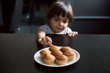Cute curious little girl looking and reaching hand taking muffins on table, hungry funny kid eager to eat cake stealing cookie while parents not watching, bakery and child addiction to sweets concept