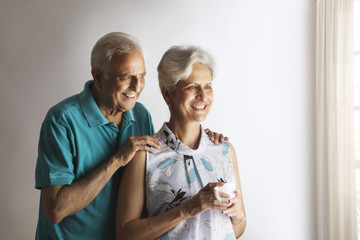Thoughtful senior couple having tea looking through window