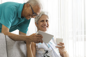 Senior man showing digital tablet to senior woman