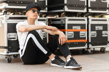 handsome stylish man with sunglasses. and a cap in a fashion white T-shirt and black pants sits near the containers on the street