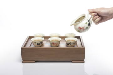 woman hand dropping a green tea isolated white.