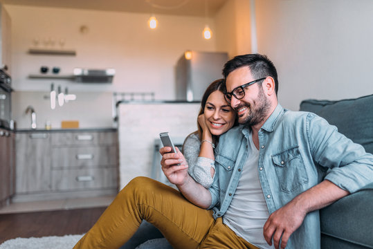 Close-up image of couple watching at smartphone screen indoors.