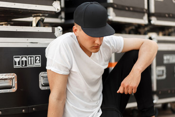 Fashion young man in a fashionable black cap with a stylish white t-shirt sitting near the boxes