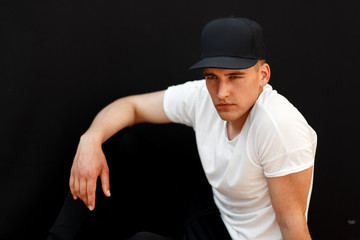 handsome stylish man in a black cap and a white T-shirt with black pants sits on a black background