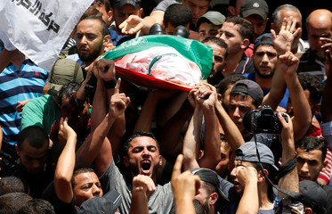Mourners shout slogans as they carry the body of a Palestinian Hamas militant who was killed in Israeli tank shelling, during his funeral in Jabaliya in the northern Gaza Strip