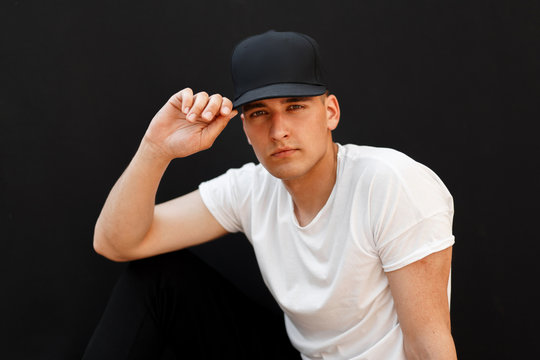 young handsome man in a fashionable black cap and white T-shirt sits on a black background