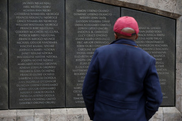 A man stands in front of a wall displaying the names of people killed in the 1998 U.S. Embassy bombing at the August 7th memorial park in Nairobi