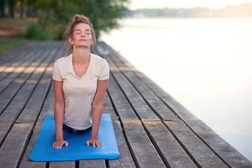 Junge Frau macht eine Yoga Übung am See