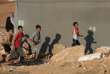 Internally displaced boys run outside a tent in Idlib province