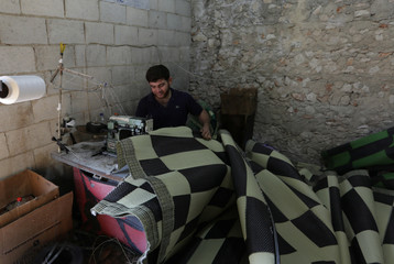A man works on woven mats inside a factory in Idlib province