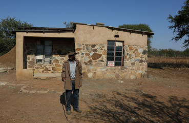 A villager looks on outside his house in Moruleng, a small mining community, in Rustenburg