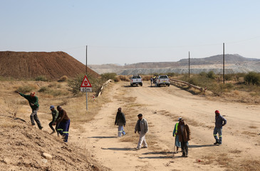 Villagers of Moruleng, a small mining community, leave after speaking to mining authorities outside a mine in Rustenburg