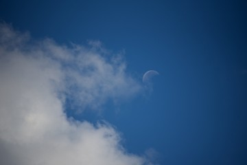 Moon on the blue sky background. Sky with white clouds.