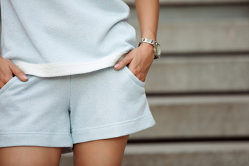 Cropped shot of woman hands in shorts pocket, watches on wrist