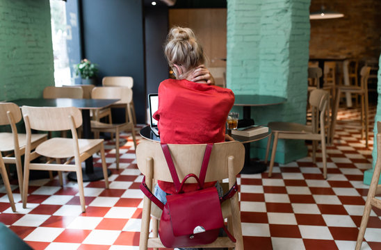 Vintage blonde girl with a bow and red shirt using her phone while smile in a coffee bar