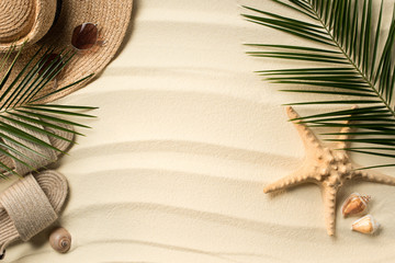 flat lay with palm leaves, straw hat and flip flops on sandy beach