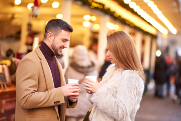 A beautiful young couple drinking mulled wine in a christmas market.