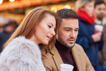 Portrait of a beautiful young couple drinking mulled wine in a christmas market.