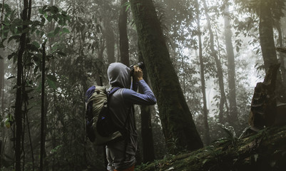 traveler photographing with backpack and enjoying a beautiful nature forest.