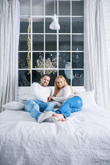 A beautiful happy young couple laying on the bed with christmas lights in the background.