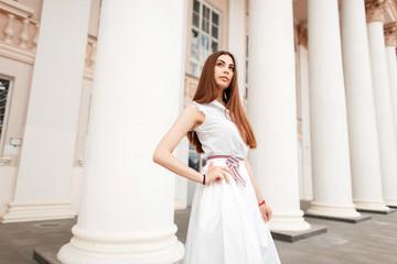 Fashion beautiful model woman in white fashionable dress near old white columns