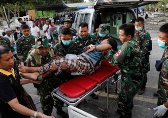 Indonesian soldiers lift up an injured woman after arriving at Tanjung hospital after earthquake hit on Sunday in North Lombok