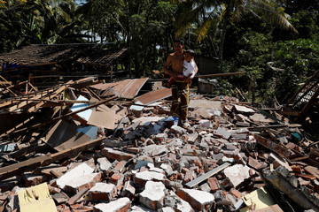 A man holds his child as he walks through the ruins of their house at Kayangan district after earthquake hit on Sunday in North Lombok