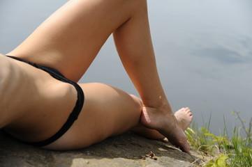 schlanke frau sonnt sich am see beine bikini