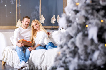 A beautiful happy young couple sitting on the sofa in the living room with the christmas tree and giving presents to each other.