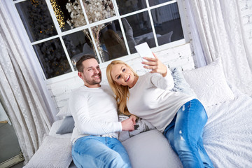 A beautiful happy young couple laying on the bed at christmas and taking a selfie.