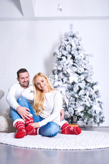 A beautiful happy young couple sitting on the ground and hugging each other with the christmas tree and the presents.