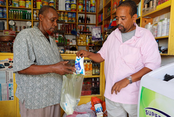 Nuradin Haji Omar, a shopkeeper sells milk from Holstein Friesian cows, to a client at his retail shop in the outskirts of Mogadishu